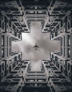 B&W Aeroplane flying among buildings from the floor-01